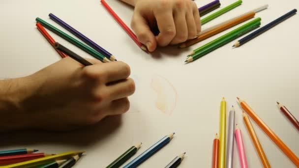 Zblízka mužských a ženských rukou, přičemž barevné tužky a přibližování