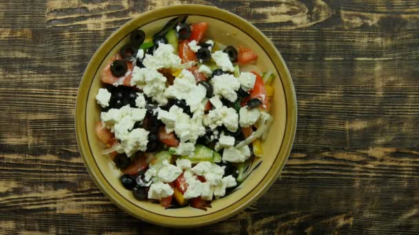 Ženská ruka posypeme kořením z dřevěnou lžící na vegetariánské nízkokalorické Řecký salát. pohled shora detail