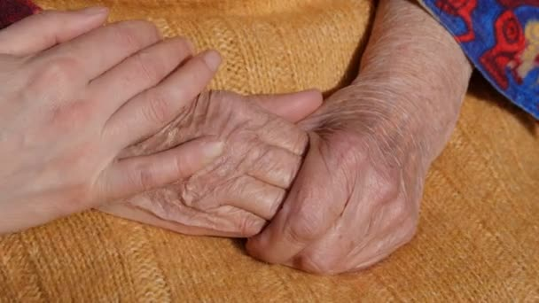 Mladý mans a Zenske ruce, uklidňující staré pár rukou babička venkovní.