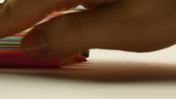 Nő vesz rózsaszín ceruza, és támaszkodva a fehér könyv