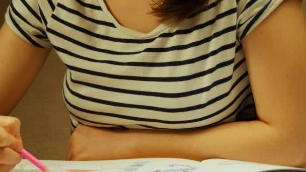 Mladá žena drží tužku a nakreslí doma. Omalovánky pro děti a dospělé. Pro odbourání stresu. Dospělé omalovánky