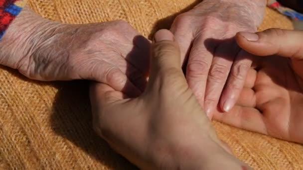 Mladý samec ruce uklidňující postarší pár rukou babička venkovní zblízka.