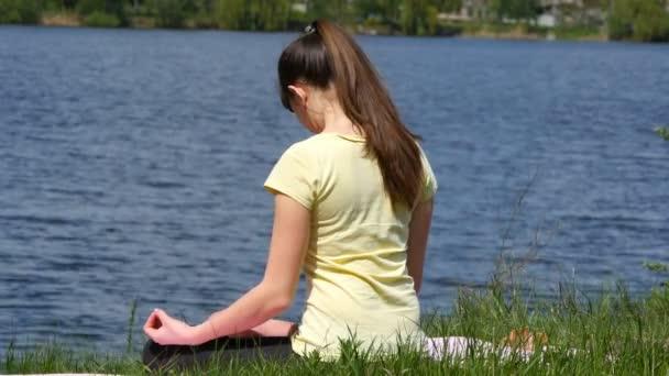 Mladá žena dělá cvičení ohýbá hlavou fro. Dívka sedící v trávě a meditují vedle řeky dělat cvičení jógy v lotosové pozici