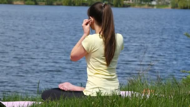 Young woman putting earphones in her ears and meditating in lotus position. Girl sitting on the grass and relaxing meditating on the beach beside the river