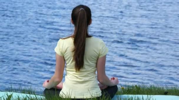 junge Frau beim Meditieren am Strand. Mädchen sitzt auf dem Gras und meditiert neben dem Fluss und macht Yoga-Übungen während der Lotusposition