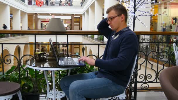 Young man in glasses are sitting at table in shopping mall and working on a laptop