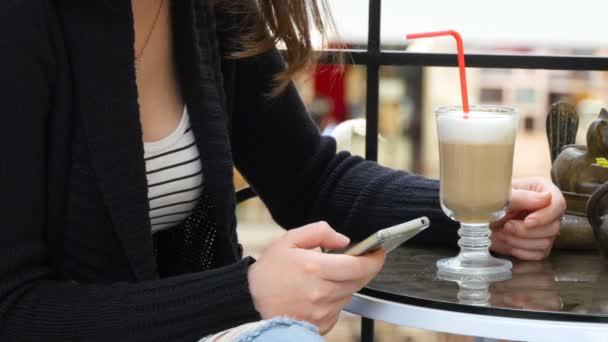 Ženské ruce pomocí smartphone a s cappuccino Café v nákupní centrum. Detail dívky, informace o prohlížení a posouvání obrázků na smartphonu