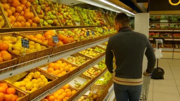 Muž s nákupní košík zvolit pomeranče v hypermarketu