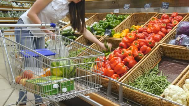 Mladá žena tlačí vozík podél uliček s potravinami v supermarketu. Dívka, výběr čerstvé zeleniny v obchodu s potravinami a jejich uvedení v nákupním vozíku. Žena, nákup papriky v obchodě