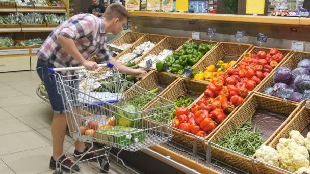 36a1d34de0 Jovem empurrando o carrinho ao longo de corredores do supermercado no  supermercado. Cara escolher legumes frescos ...