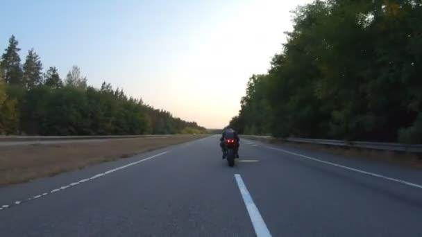 Sledujte motorkáře na moderní sportovní motorce na venkovské silnici. Motorkář závodní jeho motocykl na dálnici. Chlápek, co jezdí na kole. Pojem svoboda a dobrodružství na cestě. Letecký snímek