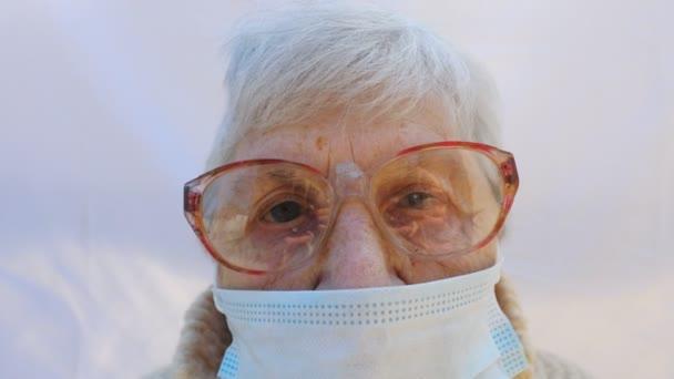 Porträt einer Oma mit Schutzmaske vor dem Virus. Eine ältere Dame blickt in die Kamera und zeigt traurige Gefühle. Konzept der Gesundheit und Sicherheit Leben vor einer Pandemie. Coronavirus-Quarantäne für alte Menschen