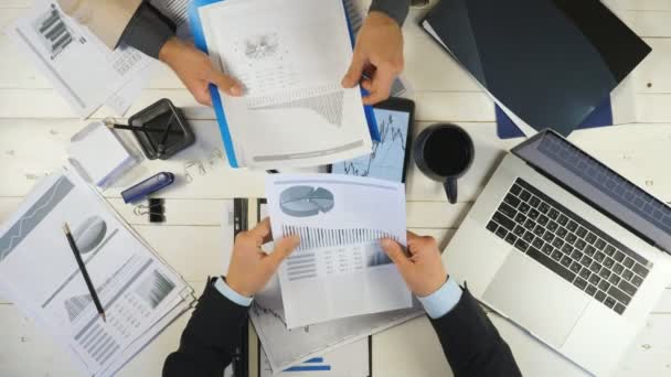 Top view male hands of two young businessmen checking graphs and discussing financial reports in office. Successful business colleagues sitting at table and developing a new business project