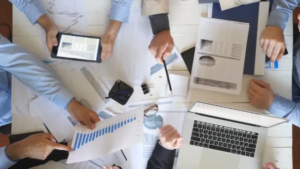 Top view male and female hands of business people planning strategy for corporate project in office. Business team checks financial graphs at desk. Colleagues sitting at table and examining documents