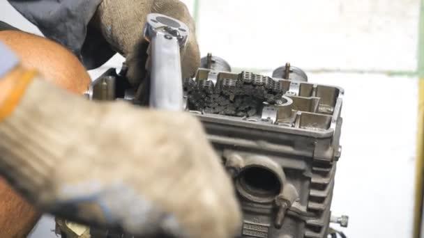Nerozpoznatelný mechanik opravující automobilový motor pomocí nářadí. Auto master opravuje motor z vozidla. Muž, který se stará o údržbu auta. Opravář pracující v garáži nebo dílně. Uzavření pomalého pohybu
