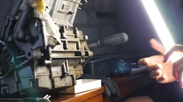 Mechanické upevnění automobilového motoru v garáži nebo dílně. Opravář se pustil do servisu auta. Muž, který používá pro svou práci jasnou baterku ve tmě. Uzavření pomalého pohybu
