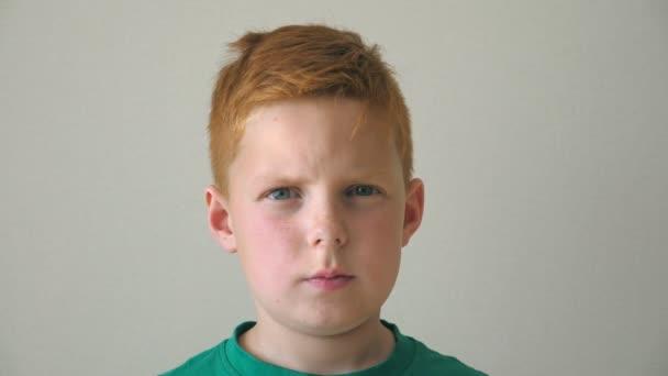 Portrét vážného zrzavého hocha s pihami. Roztomilé pohledné dítě hledící do kamery uvnitř. Zblízka emoce mužského dítěte se smutným výrazem na tváři. Zpomalený pohyb