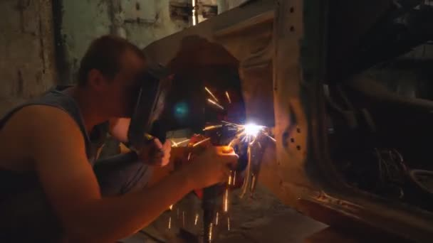 Repairer wearing protective mask welding some auto detail. Mechanic working in garage or workshop. Man engaged servicing vehicles. Bright sparks flying around in dark. Car repair concept. Dolly shot