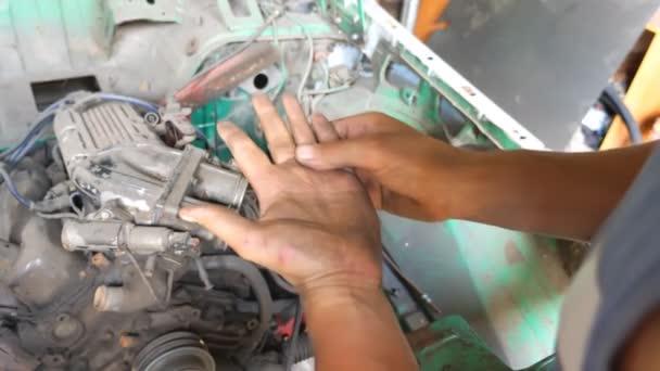 Mechanik ukazuje ruce v topném oleji po upevnění auta. Auto master tření špinavé dlaně po tvrdé práci v garáži nebo dílně. Muž zapojený do servisu. Zavřít Zpomalený pohyb