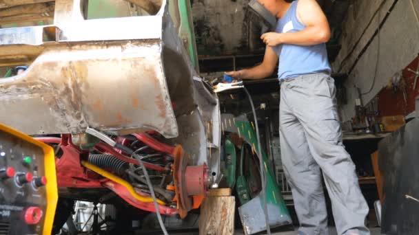 Nízký pohled na profesionální servisní svařování auto detaily pomocí ochranné masky. Umělý mechanik opravující automobil. Muž se zabývá servisem auta v garáži nebo dílně. Koncept údržby vozidla