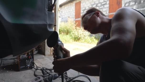 Mechanik nosí ochranné brýle leštění auto s elektrickým nářadím v garáži. Dovedný mechanik obnovuje automobil. Chlápek mlející karoserii starého auta pomocí brusky. Muž v servisním voze