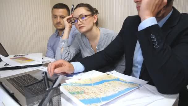 Eine Gruppe junger Geschäftsleute sitzt am Tisch in einem modernen Büro und arbeitet an einem neuen Projekt. Die Kollegen schauen während des Arbeitsprozesses sorgfältig auf den Laptop-Bildschirm. Büroangestellte mit Geschäftsentwicklung beschäftigt