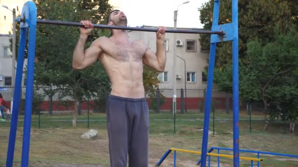 Young sportsman doing pull ups at sports ground. Muscular athlete exercising on horizontal bar at playground. Strong sporty man training outdoor. Concept of sportive lifestyle. Close up Slow motion