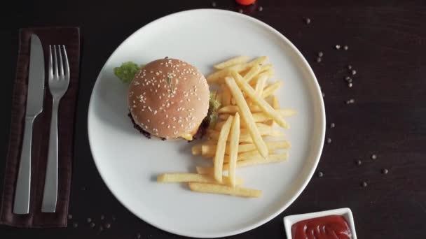 Pohled shora na burger a hranolky na bílém talíři