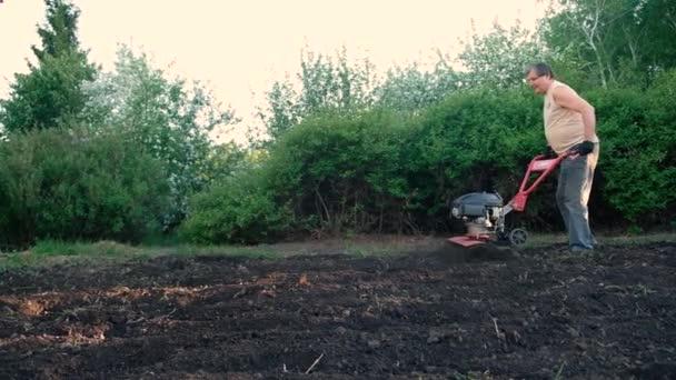 Der Mensch pflügt den Boden mit dem Grubber um. Hinterherfahrender Traktor, Motorblock im Garten. Vorbereitung für die Bepflanzung.
