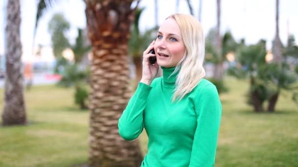 Fiatal lány beszél mozgatható sejt telefon mosolyogva, a szabadban. Boldog asszony
