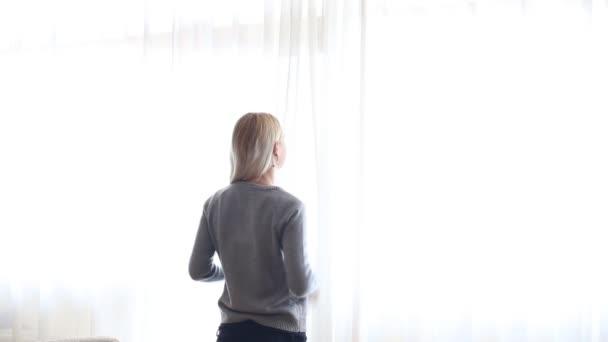 Krásy dívka otevírá záclony na velké okno a nechat světlo v místnosti. Při pohledu z okna