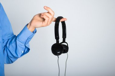 man's hand holding stylish headphones. advertising concept, isolated on a gray background.