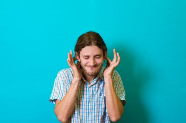 young man cleverly covers his ears