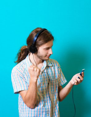 Nice music for good mood. Handsome young man in headphones holding MP3 player and looking at it while standing