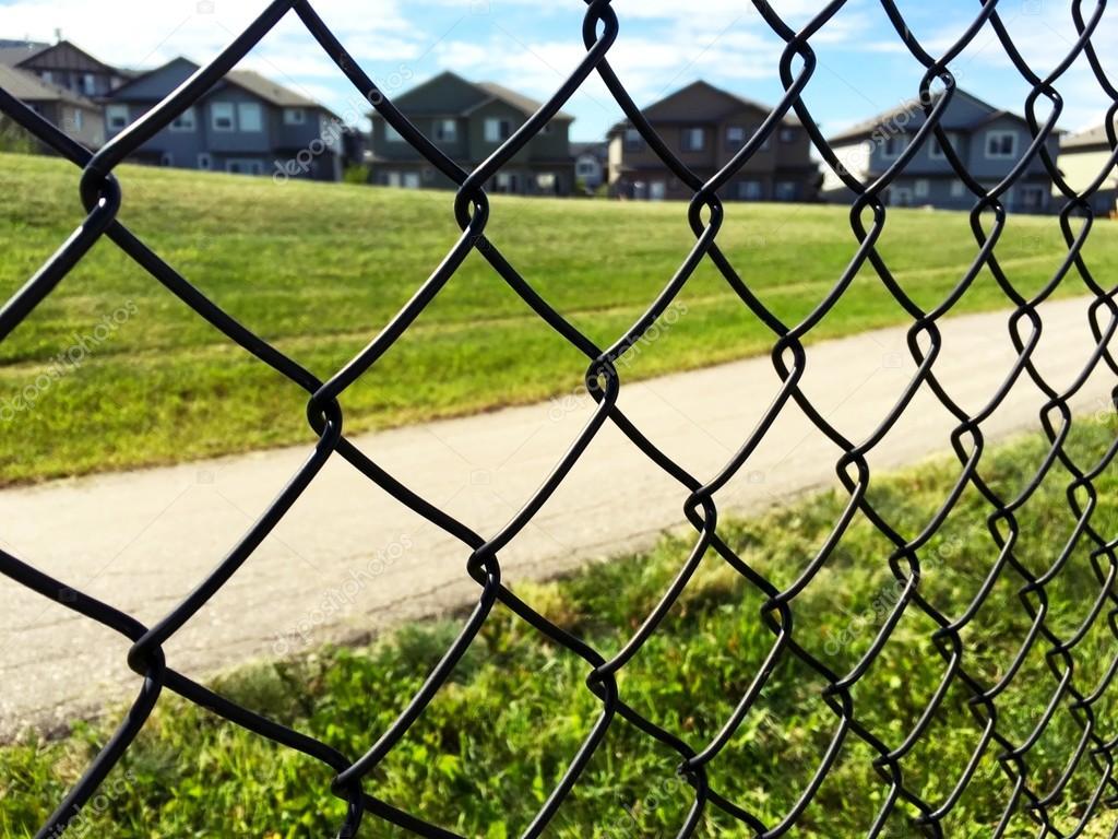 Kette Zaun am grünen Rasen, Häuser und Himmelshintergrund ...