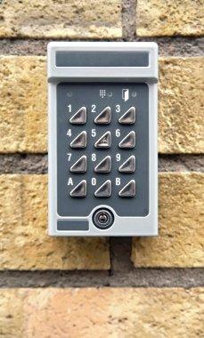Door security key pad on brick wall