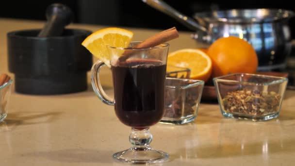 Ein Glas Glühwein mit Orange dampft
