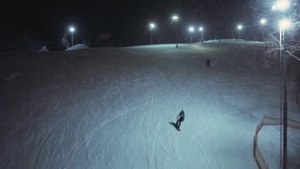Aerial shot snowboarders and skiers ride on a snow slope