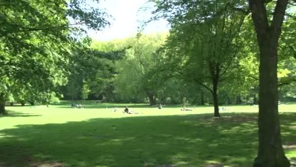 Schöner Park in Berlin mit Büschen, Bäumen und Blumen. Spaziergänger ruhen sich auf Bank und Rasen aus