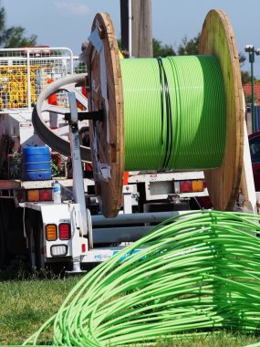 Green NBN fiber optic cable piled up behind an installation truck