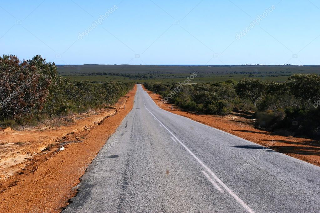 Sealed outback road lined with red earth and bushed leading towards horizon