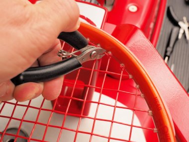 Cutting the excess of a cross strings starting knot of a Tennis racquet