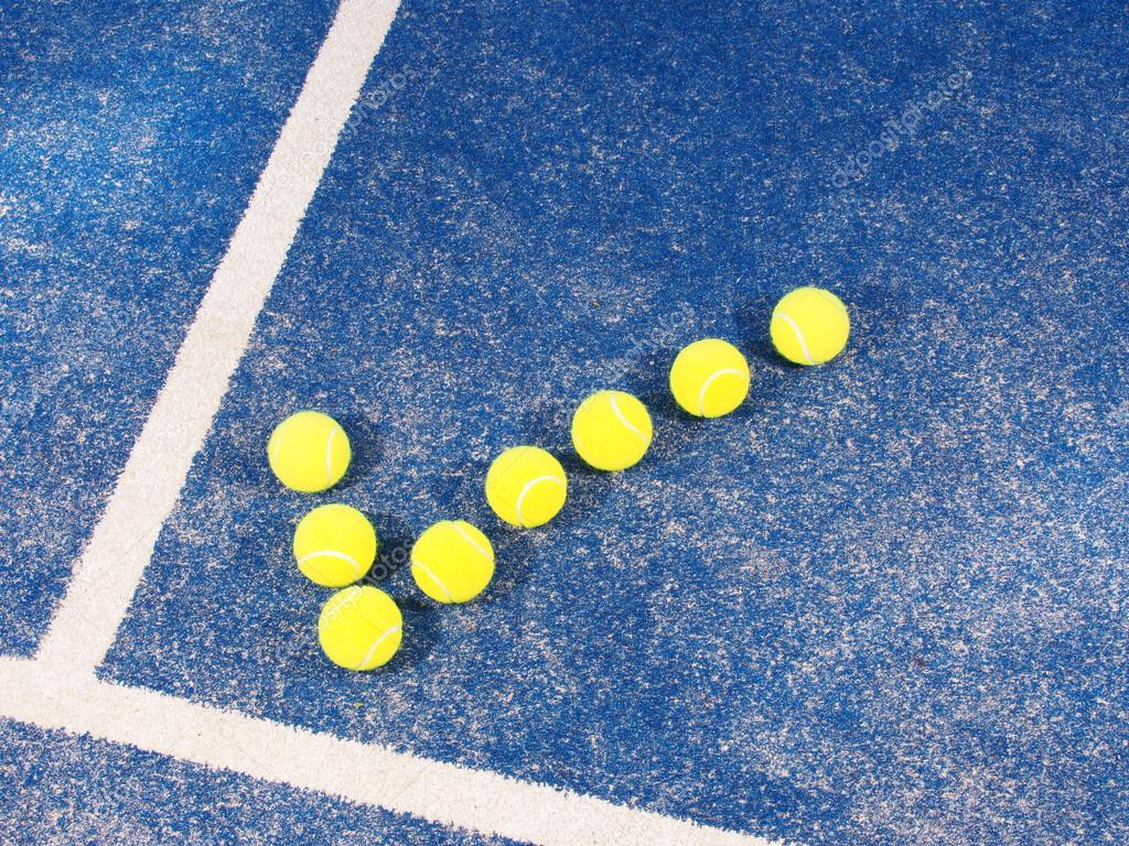 Tick symbol of Tennis balls a pristine blue artificial grass court