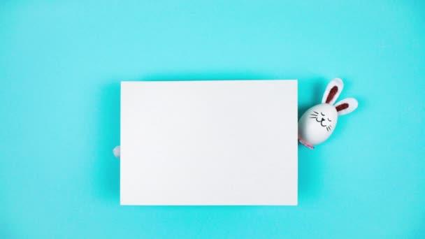 4k Három húsvéti nyuszi fehér tyúktojásból előbújik egy fehér papírlap mögül. Boldog Húsvét napi koncepciót. Világoskék háttér. Ünnepi üdvözlőlap. Állítsd le a mozgást. Fénymásolási hely.