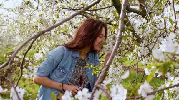 woman smelling blooming tree