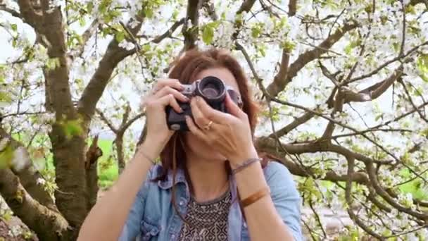 woman taking photos of blooming tree