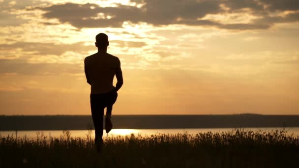 Silhouette of young sportive man practicing yoga at sunset. Slow motion.
