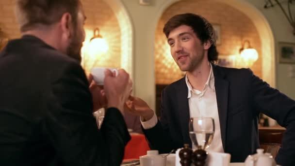 Geschäftsessen. zwei junge erfolgreiche Geschäftsleute diskutieren Ideen im Café. Zeitlupe.