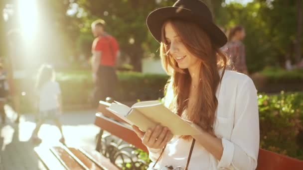 Krásná mladá dívka v klobouku čtení knih v městském parku. Zpomalený pohyb