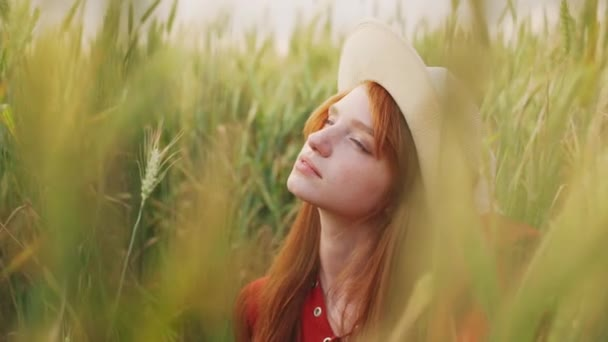Young beautiful girl with foxy hair in red dress and hat walking in field. Slow motion.